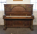 Piano for sale. An 1892, Erard upright piano with a Renaissance style walnut case with gilt accents. Cabinet features ancient Roman elements including doric columns, rosettes and a front panel carved with myrtle