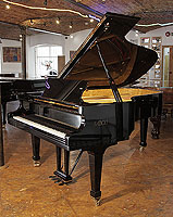A 2006, Fazioli F212 grand piano with a black case and spade legs. Piano features a slow fall mechanism