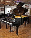 Piano for sale. A 2006, Fazioli F212 grand piano with a black case and spade legs. Piano features a slow fall mechanism.