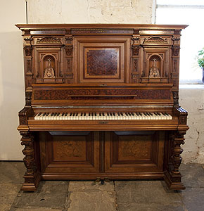A German upright piano with a Neoclassical style walnut case and cup and cover legs. Cabinet features ornately carved pilasters in high reief and copper sconces in a sea monster design.