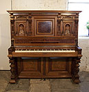 Piano for sale. A German upright piano with a Neoclassical style walnut case and cup and cover legs. Cabinet features ornately carved pilasters in high reief and copper sconces in a sea monster design.