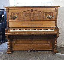 A Helmholz upright piano for sale with a Romanesque style, oak case and barley twist legs. Cabinet features a front panel ornately carved with rounded arches and grotesque heads on piano cheeks