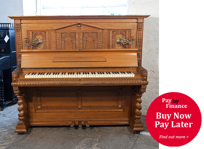 Helmholz upright piano for sale with a Romanesque style, oak case and barley twist legs. Cabinet features a front panel ornately carved with rounded arches and grotesque heads on piano cheeks.