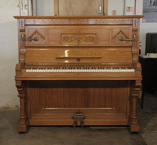 An 1895, English Gothic style, Ibach upright piano for sale with a carved, oak case and inlaid panels featuring traditional folk art motifs