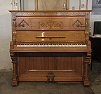 Piano for sale. An 1895, English Gothic style, Ibach upright piano with a carved, oak case and inlaid panels featuring traditional folk art elements.