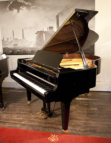 Piano for sale. A 2017, Kawai GL-50 grand piano for sale with a black case and square, tapered legs. Keyboard lide features a slow fall mechanism. Piano has an eighty-eight note keyboard and a three-pedal lyre.