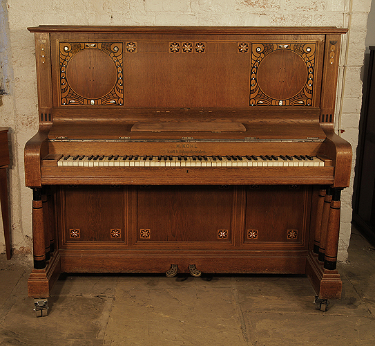 Kohl upright piano for sale with a walnut case and three turned, column legs. Entire cabinet inlaid with contrasting ebony and mother of pearl in a stylised floral design