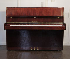 A Neumayer upright piano with a mahogany case