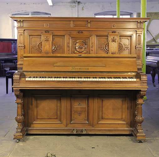 Neumeyer upright piano for sale with a walnut case and cup and cover, turned legs. Entire cabinet features elaborate carvings.