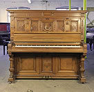 Piano for sale. Antique, Neumeyer upright piano for sale with a walnut case and cup and cover, turned legs. Entire cabinet features elaborate carvings of scrolls, acanthus, cabuchons, rosettes and gadrooning