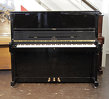 A 2004, Petrof upright piano with a black case and polyester finish