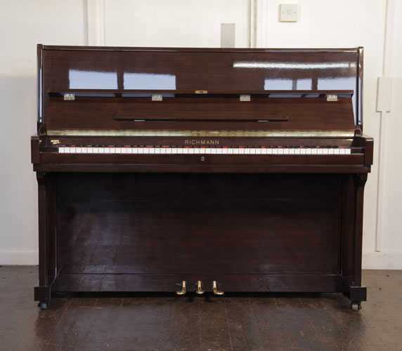 Richmann upright piano with a mahogany case. Piano has an eighty-eight note keyboard and three pedals.