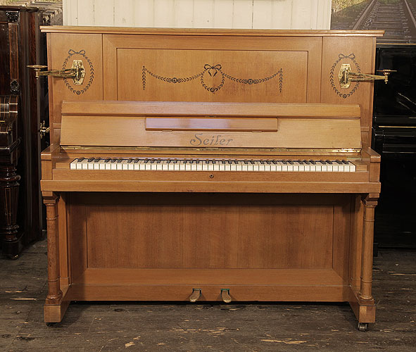 A 1911, Seiler upright piano for sale with a walnut case and two turned, column legs. Cabinet inlaid with contrasting ebony with stylised flowers, swags and bows