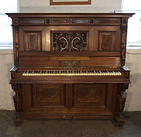 An 1898, Steingraeber upright piano with a Neoclassical style, carved walnut case and cup and cover legs. Cabinet features a front panel carved with acanthus and dragon heads in high relief.