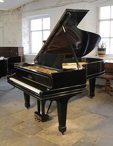 An unrestored, 1902, Steinway Model B grand piano with a black case and spade legs. Piano has a three-pedal lyre and an eighty-eight note keyboard.