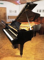 A 1974, Steinway Model B grand piano with a black case and spade legs.