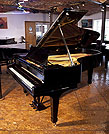 Piano for sale. A 1925, Steinway Model C grand piano with a black case and spade legs. Piano has an eighty-eight note keyboard and a three-pedal lyre.