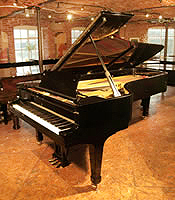 A 1955, Steinway & Sons Model D concert grand piano with a black case and spade legs