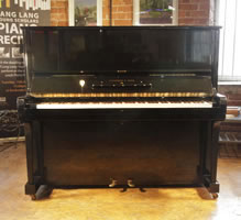 A 1939, Steinway Model K upright piano with a black case and brass fittings