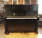 Piano for sale. A 1939, Steinway Model K upright piano with a black case and brass fittings. Piano has an eighty-eight note keyboard and two pedals