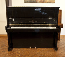 A 1985, Steinway Model K upright piano with a black case and brass fittings.