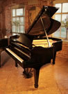 A 1936, Steinway Model M grand piano with a black case and spade legs. Piano has an eighty-eight note keyboard and a two-pedal lyre.