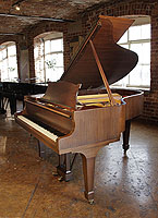 A 1961, Steinway Model M grand piano with a satin, walnut case and spade legs. Piano has an eighty-eight note keyboard and a two-pedal lyre.