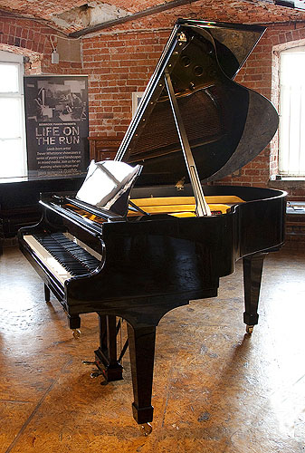 A 1951, Steinway Model S baby grand piano with a black case and spade legs. Piano has an eighty-eight note keyboard and a two-pedal lyre.