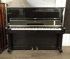 A 1961, Steinway Model V upright piano with a black case and brass fittings.