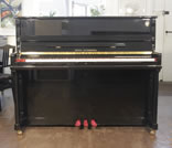 Piano for sale. A brand new Steinberg Model AT-K18 upright piano with a black case and slow fall mechanism.