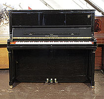A Brand new, Wilh Steinberg Model AT-K30 upright piano with a black case and brass fittings.