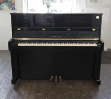 A Yamaha ET121 upright piano for sale with a black case and brass fittings