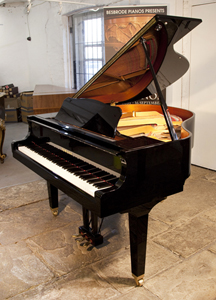 A 2015, Yamaha GB1 baby grand piano for sale with a black case and square, tapered legs. Made in Japan. Piano has an eighty-eight note keyboard and a three-pedal lyre.