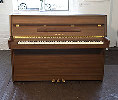 A 1986, Yamaha LU-101 upright piano with a satin, walnut case