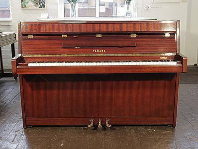A 1970, Yamaha upright piano with a mahogany case and polyester finish