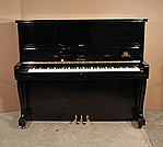 Piano for sale. Atlas Mod A20 upright piano with a black case and cabriole legs. Piano has an eighty-eight note keyboard and three pedals.