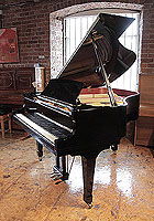 A 1998, Boston GP163 II baby grand piano for sale with a black case and spade legs. Piano has an eighty-eight note keyboard and a three-pedal lyre.