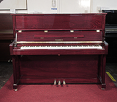 A brand new, Feurich Model 122 upright piano with a mahogany case and brass fittings