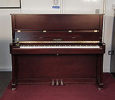 A brand new, Feurich Model 122 upright piano with a satin, walnut case and brass fittings