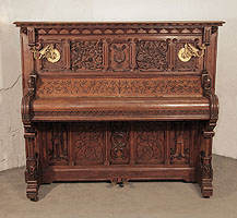 Renaissance style, Gebruder Knake upright piano for sale with an ornately carved, oak case. Cabinet features front panels carved with arabesque style, flowers, foliage and a central lyre. Seated dragons recline at the base of the Classical columnar, piano legs. Gothic tracery and arches feature strongly throughout the cabinet architecture.
