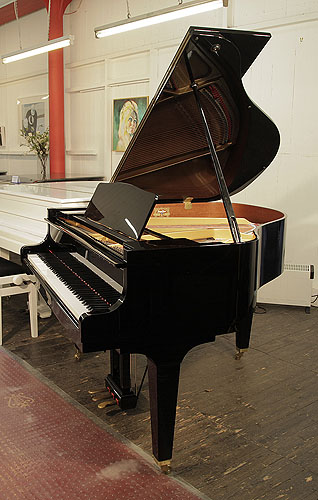 Piano for sale. A 2014, Kawai GM-10 baby grand piano for sale with a black case and square, tapered legs. Piano has an eighty-eight note keyboard and a three-pedal lyre.