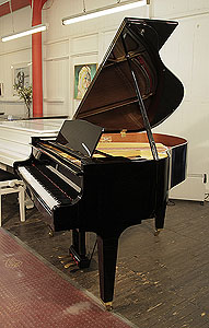 A   Kawai GM-10 baby grand piano for sale with a black case and square, tapered legs. Piano has an eighty-eight note keyboard and a three-pedal lyre.