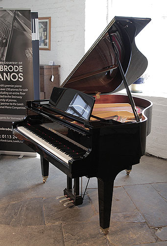 Piano for sale. A 2015, Kawai GM-10K baby grand piano for sale with a black case and square, tapered legs. Piano has an eighty-eight note keyboard and a three-pedal lyre.