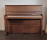 Piano for sale. A Sauter upright piano with a satin, walnut case. Piano has an eighty-eight note keyboard and three pedals.