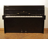 Piano for sale. A 1961, Steinway Model F upright piano with a black case and brass fittings. Piano has an eighty-eight note keyboard and two pedals.
