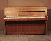 Piano for sale. A 1965, Steinway Model F upright piano with a polished, walnut case. Piano has an eighty-eight note keyboard and two pedals.