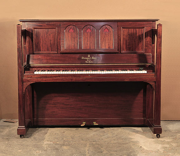 Arts and Crafts style,  1905, Steinway  upright piano for sale with a figured, mahogany case and large sculptural legs. Cabinet features a music desk in a three arche design with cut-out inverted hearts backed with red felt