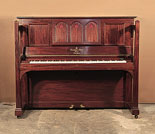 Arts and Crafts style, 1905, Steinway upright piano for sale with a figured, mahogany case and large sculptural legs. Cabinet features a music desk in a three arch design with cut-out inverted hearts backed with red felt. Piano has an eighty-eight note keyboard and two pedals.
