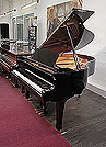 Piano for sale. A 2003, Yamaha C2 grand piano for sale with a black case and spade legs.