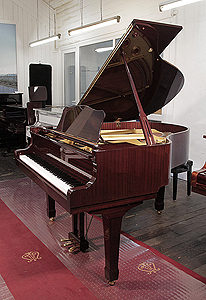 A 1993, Yamaha grand piano with a mahogany case and spade legs. Piano has an eighty-eight note keyboard and a three-pedal lyre.